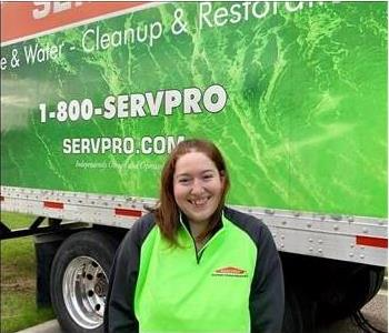 Female SERVPRO employee smiling in front of SERVPRO semi