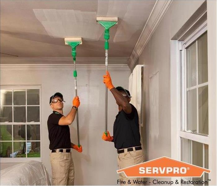 SERVPRO employees removing soot from ceiling