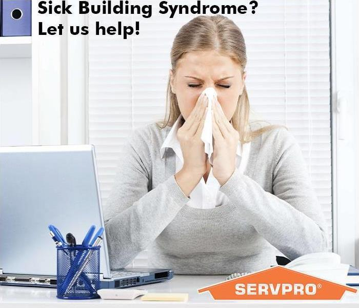 Woman blowing nose at her desk with SERVPRO logo in the background